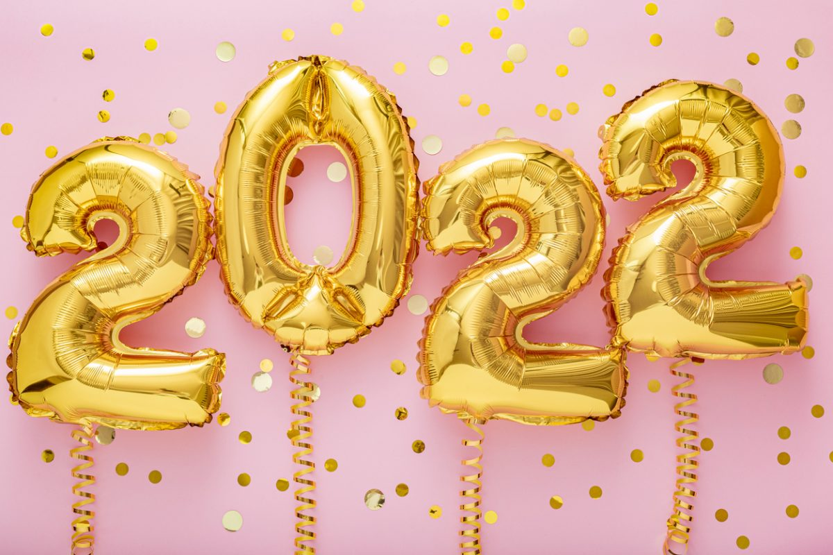2022 year gold balloons on ribbons with confetti on pink wall. Happy New year 2021 eve celebration.